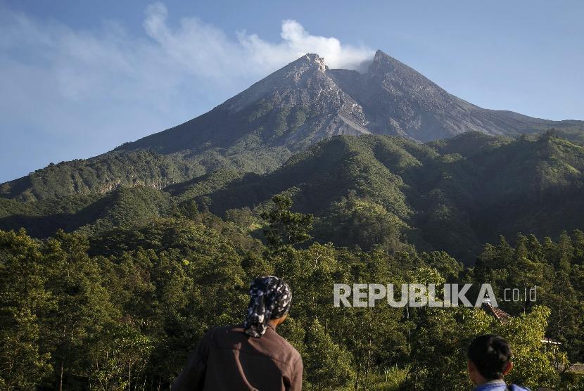 Warga mengamati puncak Gunung Merapi di pos pemantauan kawasan Bukit Klangon, Cangkringan, Sleman, DI Yogyakarta