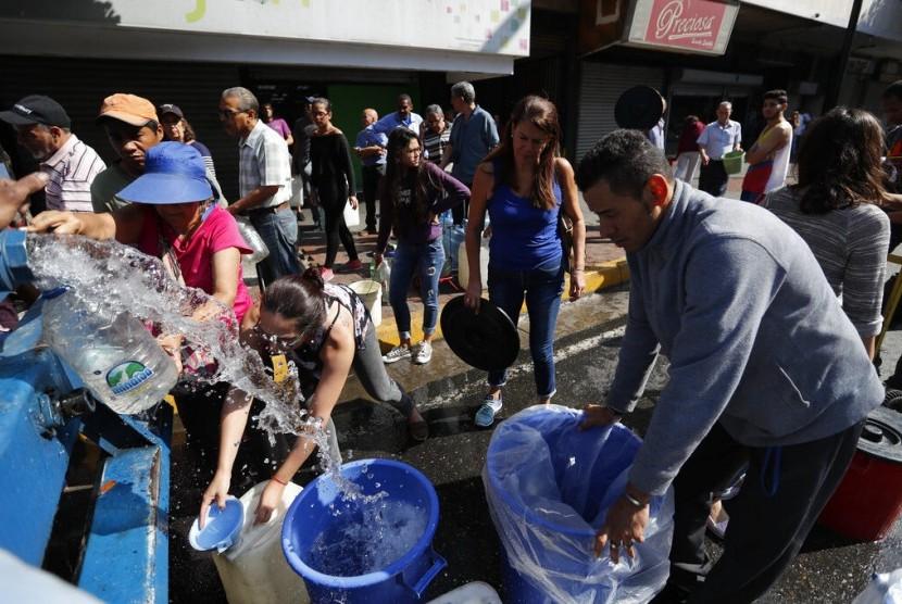 Warga mengambil air dari truk di Caracas, Venezuela, Selasa (12/3).
