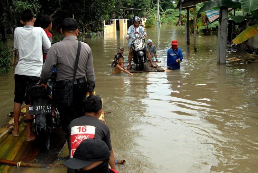 Warga mengangkut sepeda motor menggunakan rakit batang pisang saat banjir di Desa Panakkukang, Kabupaten Gowa, Sulawesi Selatan, Jumat (28/12/2018).