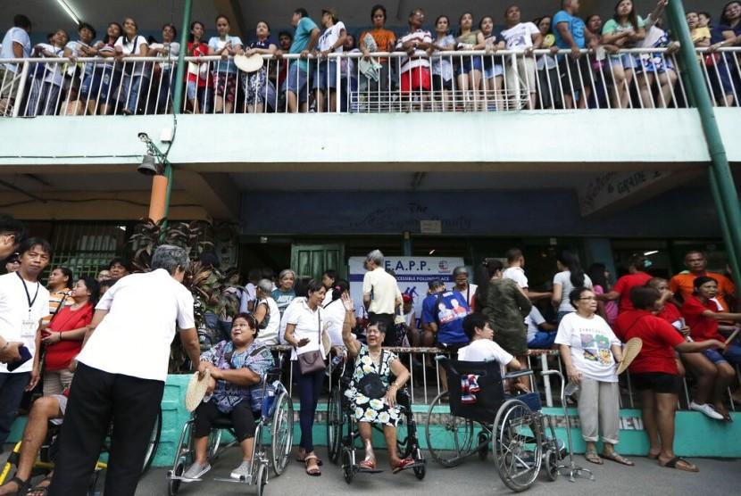 Warga mengantre untuk memberikan suara di tempat pemungutan suara di sekolah dasar Manuel L. Quezon di Manila, Filipina, Senin (13/5). Filipina menggelar pemilu paruh waktu hari ini.