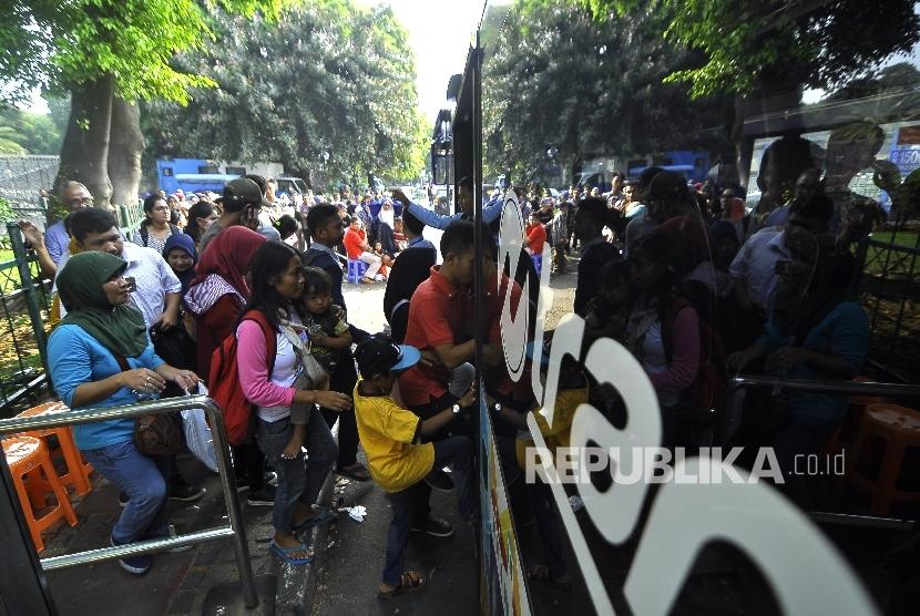 Warga mengantre untuk menaiki bus tingkat wisata di Halte Masjid Istiqlal, Jakarta Pusat, Selasa (4/7).