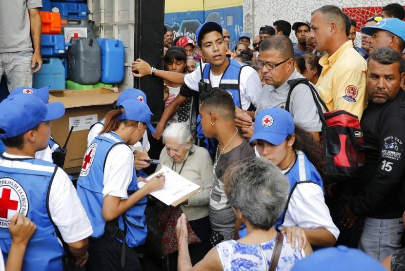 Warga mengantre air bersih dan pil pemurni air saat bantuan kemnausiaan pertama Palang Merah tiba di Caracas, Venezuela, Selasa (17/4).
