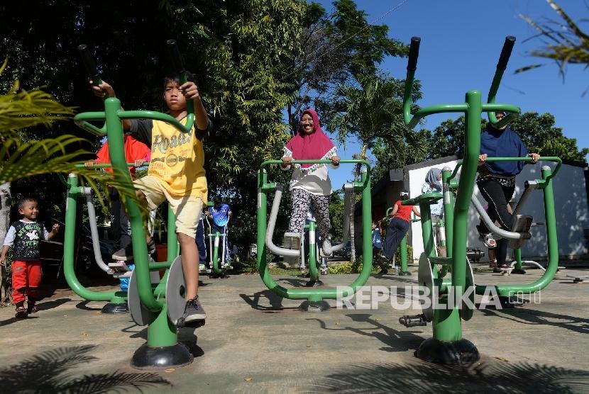 Warga menggunakan alat olahraga fitness di Komplek GOR Rawamangun, Jakarta, Ahad (9/4).