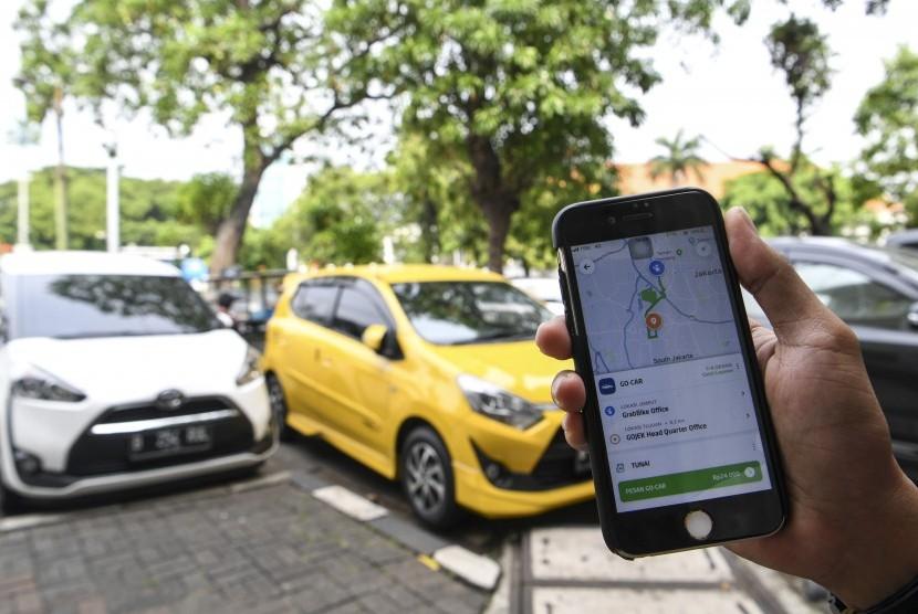 Warga menggunakan aplikasi untuk memesan taksi berbasis dalam jaringan (online) di Jakarta, Ahad (16/6/2019).