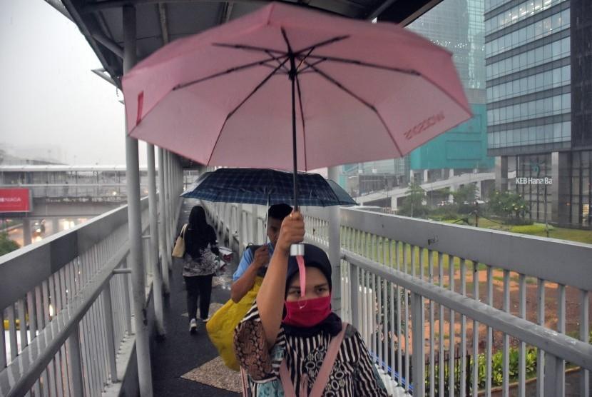 Warga menggunakan payung saat hujan mengguyur kawasan Gatot Subroto, Jakarta, Senin (11/2/2019).