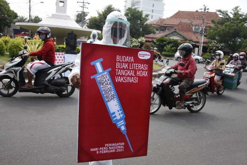 Warga mengusung poster bertajuk Peduli Literasi Anti Hoax Vaksinasi saat aksi di Jalan Gajah Mada, Solo, Jawa Tengah, Selasa (9/2/2021). Aksi tersebut digelar untuk memperingati Hari Pers Nasional sekaligus mengajak masyarakat agar bijak bersosial media dan tidak mudah menyebar berita hoax.
