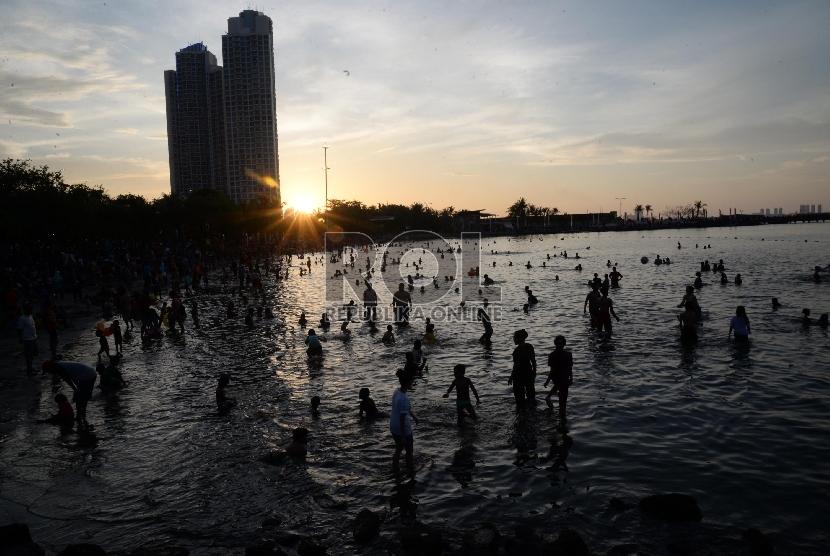 Warga menikmati pemandangan matahari terbenam di pantai Ancol, Jakarta Utara, Kamis (31/12).  (Republika/Yasin Habibi)