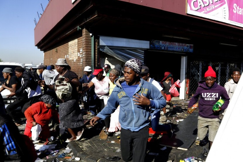 Warga menjarah sebuah toko di Germiston, di timur Johannesburg, Afrika Selatan, Selasa (3/9).