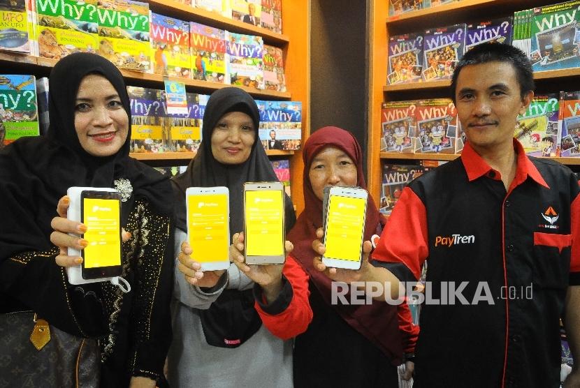Warga menunjukan aplikasi PayTren di toko buku Gramedia, Jakarta, Rabu (5/4).