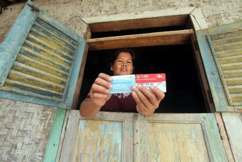 Warga menunjukan kartu peserta Program Keluarga Harapan (PKH) di Desa Gunung Sari, Citeureup, Bogor, Jawa Barat, Jumat (14/12/2018).