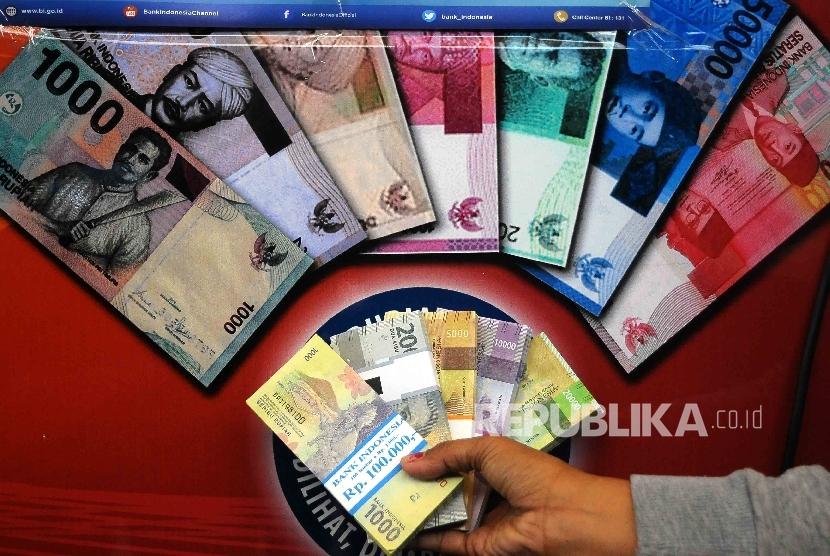 Warga menunjukan uang rupiah baru saat peluncuran uang baru di Blok M Square, Jakarta, Senin (19/12).