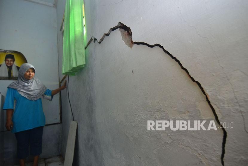 Warga menunjukkan kerusakan yang terjadi di rumahnya akibat pergerakan tanah di Desa Payung Agung, Kabupaten Ciamis, Jawa Barat, Senin (5/3).