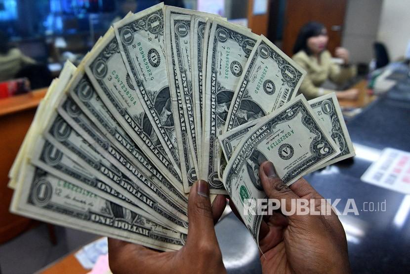 Warga menunjukkan pecahan uang dolar Amerika yang ditukarkan di salah satu gerai penukaran mata uang asing di Jakarta, Rabu (14/3).