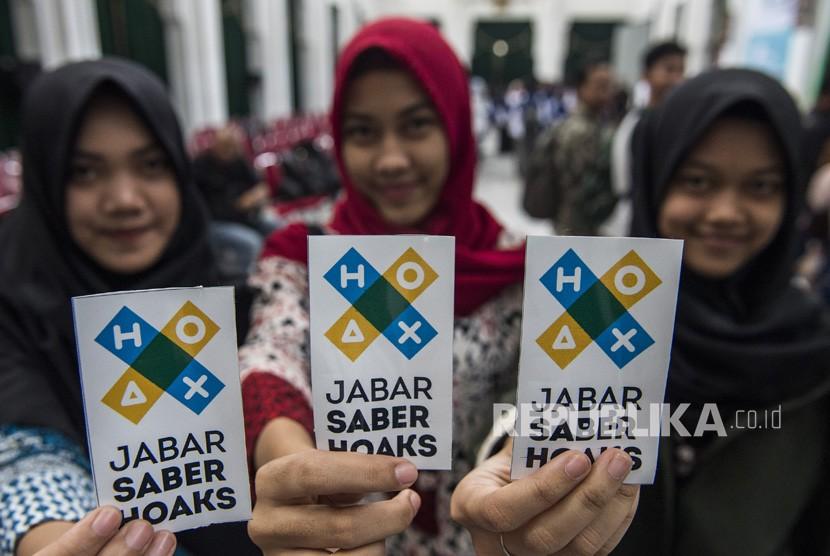 Warga menunjukkan stiker Jabar Saber Hoaks di Gedung Sate, Bandung, Jawa Barat, Jumat (7/12/2018).