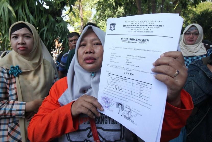 Warga menunjukkan Surat Hasil Ujian Sementara (SHUS) saat berunjukrasa di Balai Kota Surabaya, Jawa Timur, Rabu (19/6/2019).
