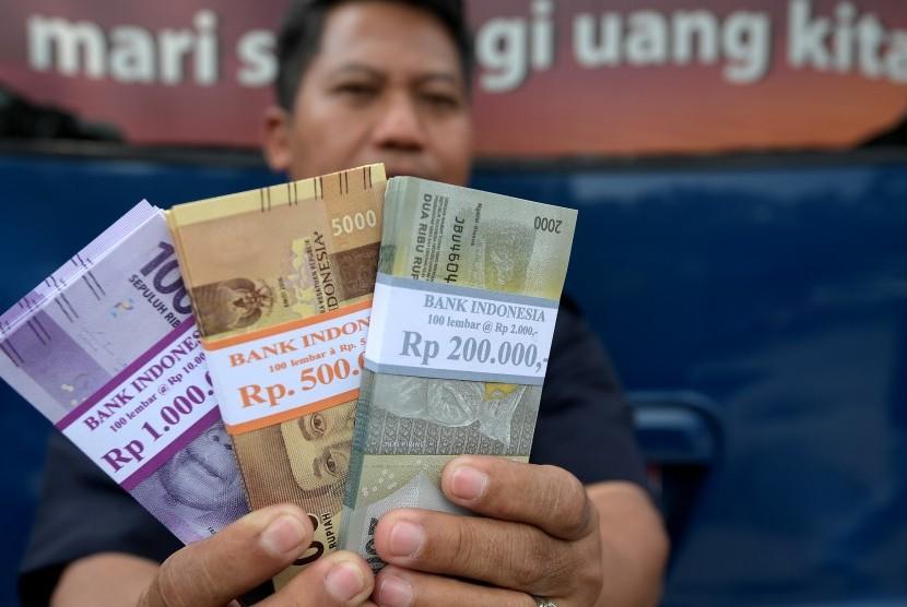 Warga menunjukkan uang pecahan yang ditukarkan dari mobil kas keliling Bank Indonesia di Lapangan IRTI, Monas, Jakarta, Senin (5/6).