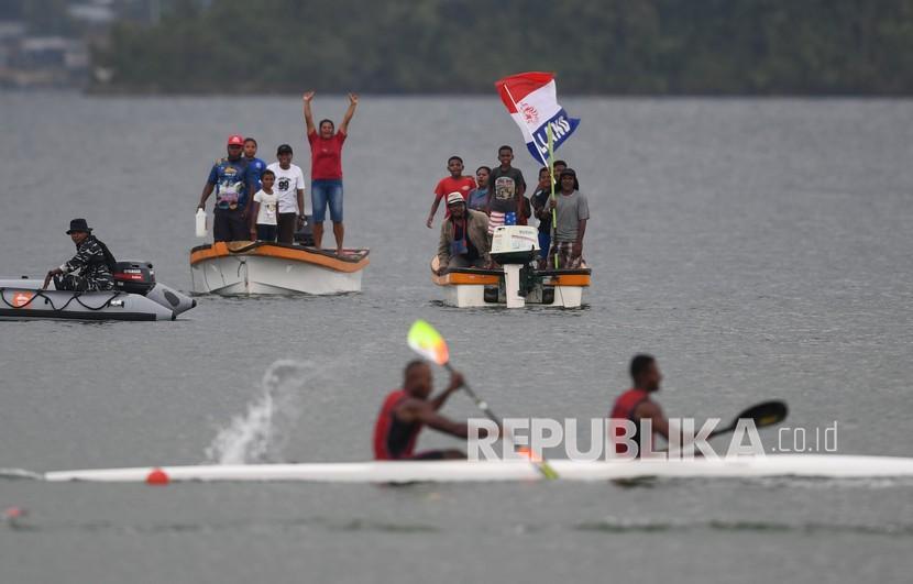 Warga menyaksikan babak semifinal canoeing 1000 meter PON Papua dari atas perahu di Teluk Youtefa, Papua, Senin (27/9/2021).