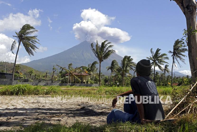 Warga menyaksikan Gunung Agung memuntahkan abu dan asap di Karangasem, Bali, Rabu (4/7).