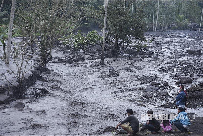 Warga menyaksikan lahar dingin yang mengalir di Sungai Yeh Sah, Rendang, Karangasem, Bali, Sabtu (2/12). Hujan deras di kawasan Gunung Agung menyebabkan lahar dingin kembali mengalir di sungai itu.