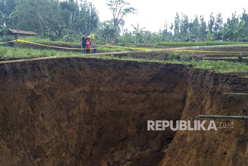 Warga menyaksikan lubang raksasa di area persawahan di Desa Sukamaju, Kadudampit, Kabupaten Sukabumi, Jawa Barat, Ahad (28/4/2019).