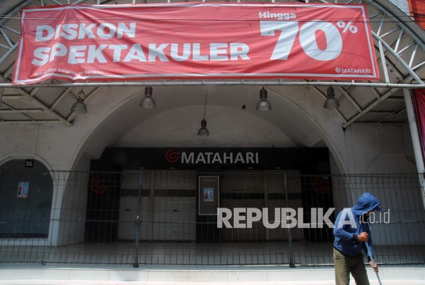Warga menyapu jalan di depan gerai Matahari Department Store Taman Topi di Jalan Kapten Muslihat, Kota Bogor, Jawa Barat, Rabu (22/9/2021), yang sudah tutup akibat pandemi Covid-19.