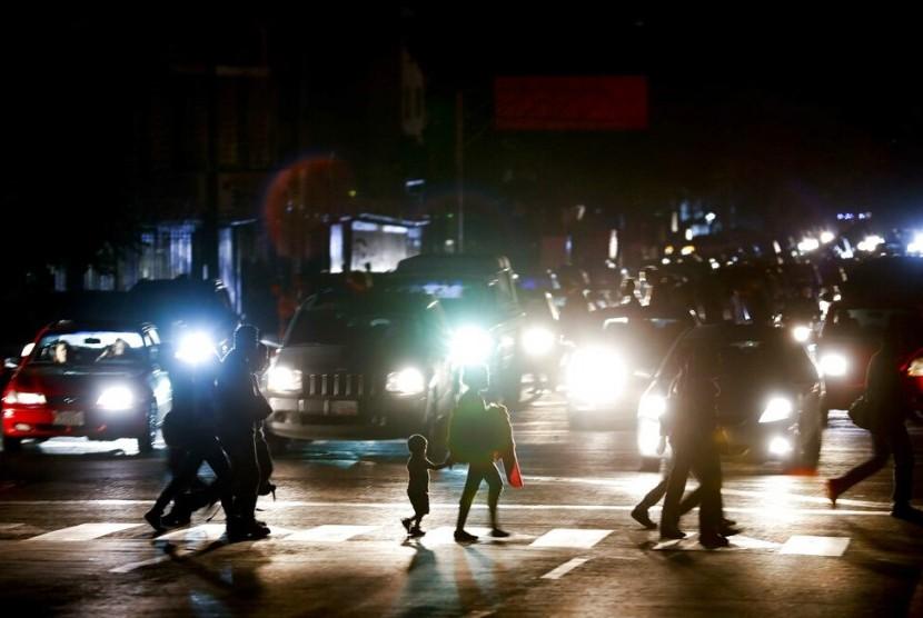 Warga menyeberang jalan di tengah kegelapan karena pemadaman listrik besar-besaran di Caracas, Venezuela, Kamis (7/3).