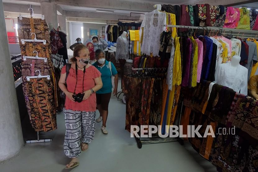 Warga Negara Asing (WNA) mengamati pakaian yang dijual di Pasar Badung, Denpasar, Bali, Jumat (23/7). Kementerian Perdagangan segera melakukan uji coba penerapan aplikasi PeduliLindungi di pasar tradisional seperti halnya di pusat perbelanjaan.