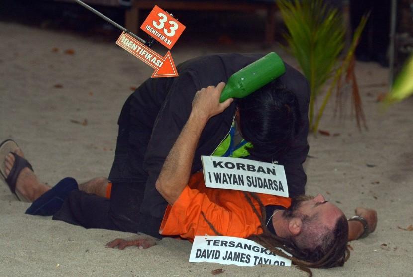 Warga negara Inggris yang juga tersangka pembunuhan polisi, David James Taylor, berkelahi dengan pemeran korban Aipda Wayan Sudarsa saat rekonstruksi di Pantai Legian, Bali, Rabu (31/8).