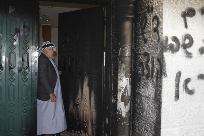 Warga Palestina berdiri dekkat pintu masjid di Deir Istiya Ramallah yang dibakar dan dicoret oleh ekstrimis Yahudi