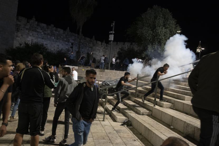 Warga Palestina bereaksi terhadap granat setrum yang ditembakkan oleh polisi Israel untuk membersihkan Gerbang Damaskus ke Kota Tua Yerusalem setelah bentrokan di kompleks Masjid Al-Aqsa, Jumat 7 Mei 2021. Jemaah Palestina bentrok dengan polisi Israel Jumat malam di situs suci suci kepada Muslim dan Yahudi, dalam eskalasi kekerasan berminggu-minggu di Yerusalem yang telah bergema di seluruh wilayah.