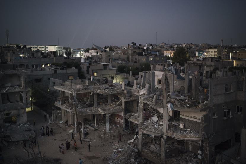 Warga Palestina berjalan di malam hari di sepanjang Jalan Al-Baali, di samping rumah-rumah yang rusak parah akibat serangan udara selama perang 11 hari antara Israel dan Hamas, kelompok militan yang menguasai Gaza, di Beit Hanoun, Jalur Gaza utara, Senin, 31 Mei 2021