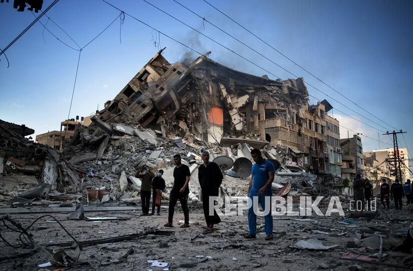 Warga Palestina berjalan di samping sisa-sisa bangunan 15 lantai yang hancur setelah terkena serangan udara Israel di Kota Gaza, Kamis (13/5).