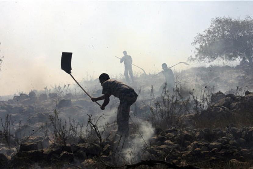 Warga Palestina berupaya memadamkan api yang membakar ladang zaitunnya akibat ulah warga pemukiman Israel..