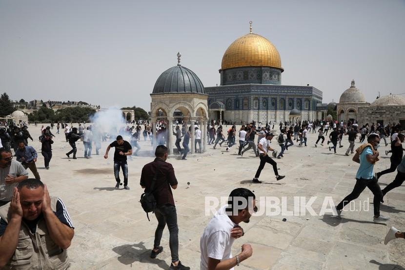 Warga Palestina lari dari bom suara yang dilemparkan oleh polisi Israel di depan kuil Dome of the Rock di kompleks masjid al-Aqsa di Yerusalem, Jumat (21/5), ketika gencatan senjata mulai berlaku antara Hamas dan Israel setelah perang 11 hari. .