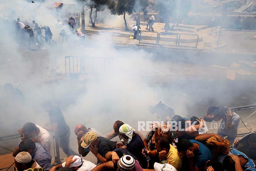 Warga Palestina melaksanakan Shalat Jumat berlarian saat kanister gas air mata yang ditembakkan polisi Israel meledak. Sebelumnya mereka melaksanakan shalat jumat  di jalan menuju di Kota Tua Yerusalem tersebut, Jumat (21/7)