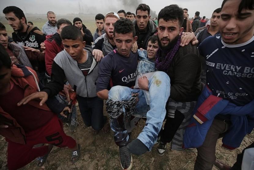 Warga Palestina menggelar demonstrasi anti-AS sambil membawa rekan mereka yang terluka terkena tembakan militer Israel, Jumat (22/12).