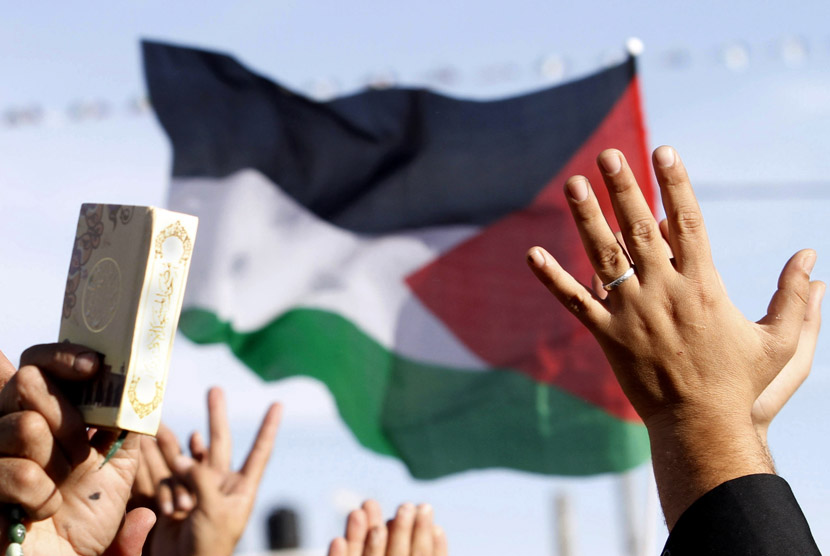 Warga Palestina mengibarkan bendera dan memegang kitab suci Alquran saat merayakan pengakuan negara Palestina oleh PBB di Ramallah. (AP/Nasser Shiyoukhi)
