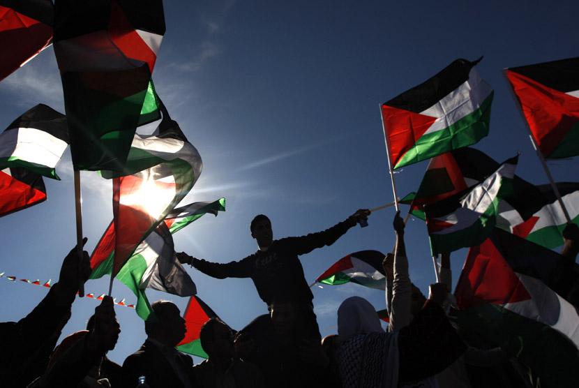 Warga Palestina mengibarkan bendera saat merayakan pengakuan negara Palestina oleh PBB di Ramallah,Ahad (2/12/2012). (AP/Majdi Mohammed)