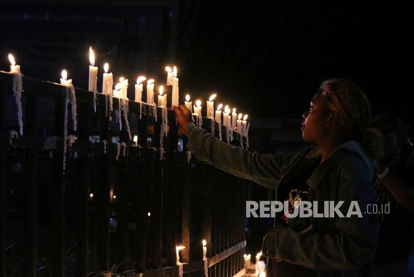 Warga Papua menyalakan lilin saat aksi damai di Bundaran Tugu Perdamaian Timika Indah, Mimika, Papua, Senin (19/8/2019).