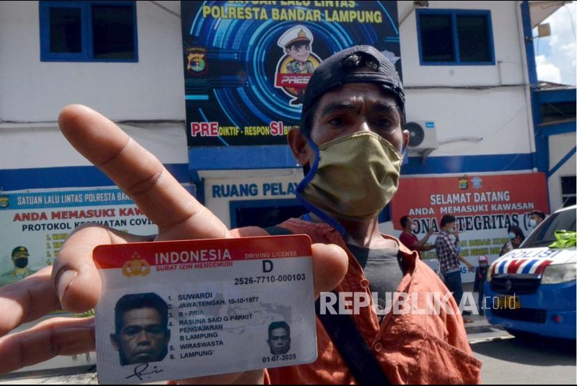 Warga penyandang disabiltas menunjukkan Surat Izin Mengemudi (SIM) D di Satuan lalu lintas Polresta Bandar Lampung, Lampung, Rabu (16/6/2021). Sebanyak 20 orang warga dengan kebutuhan khusus tersebut tetap melakukan proses tes ujian praktik dan teori untuk mendapatkan SIM D tersebut.