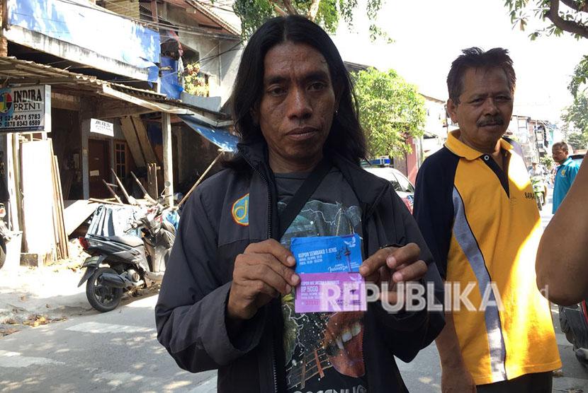 Warga RW 11 Pademangan Barat, menunjukkan kupon maut yang bisa ditukarkan dengan sembako di acara Untukmu Indonesia.