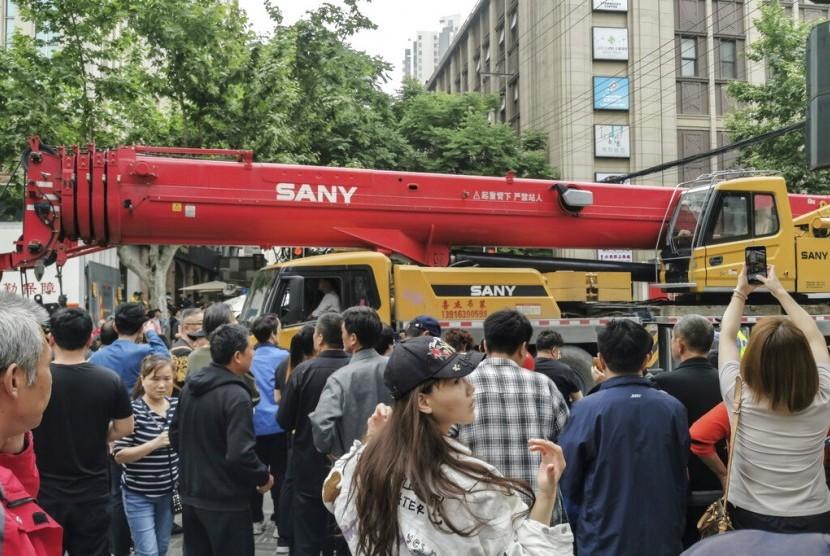 Warga sekitar menonton lokasi gedung runtuh saat kendaraan berat sedag bekerja di Shanghai, Cina, Kamis (16/5).
