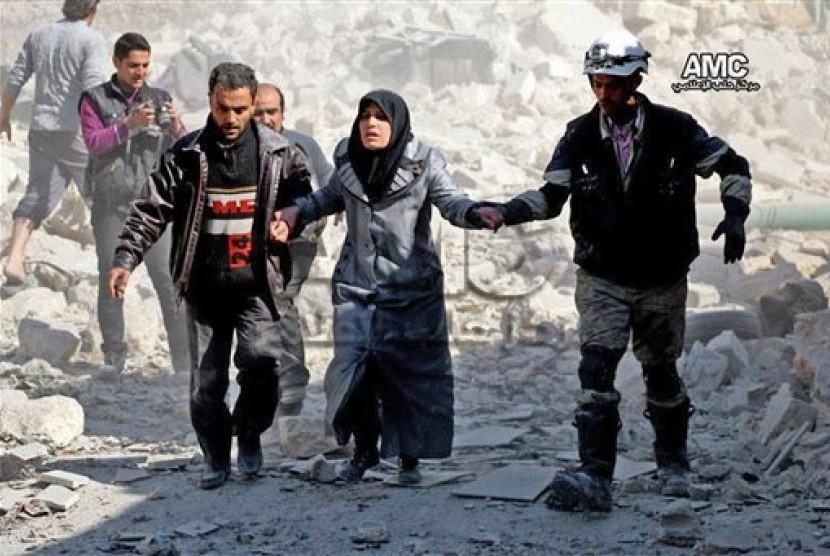Warga Suriah membantu seorang wanita yang selamat dari ledakan bom di kawasan Masaken Hanano, dekat Aleppo, Suriah.
