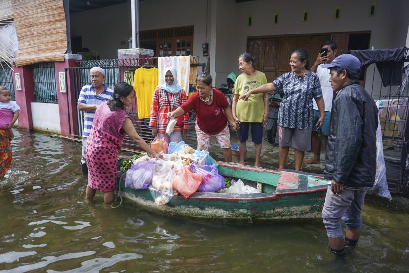 Warga terdampak banjir berbelanja di pedagang sayuran keliling yang menggunakan perahu di Pekalongan, Jawa Tengah, Senin (22/2/2021). Sejak banjir menggenangi Kota Pekalongan, pedagang berinisiatif berjualan menggunakan perahu untuk memudahkan akses melewati banjir.