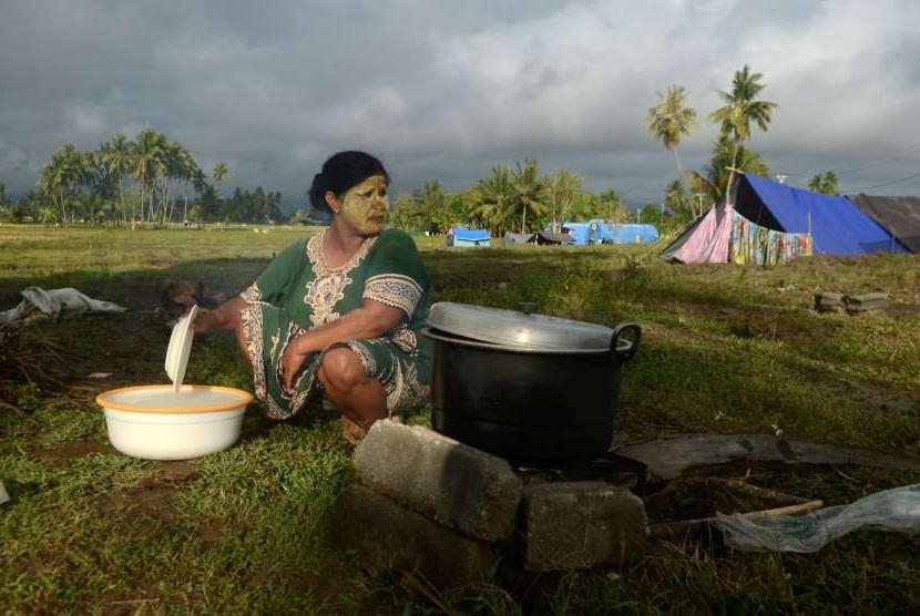 Warga terdampak gempa dan tsunami Palu-Donggala memasak di kawasan pengungsian hunian sementara yang dibangun warga di Biromaru, Kabupaten Sigi, Sulawesi Tengah, Sabtu (13/10).