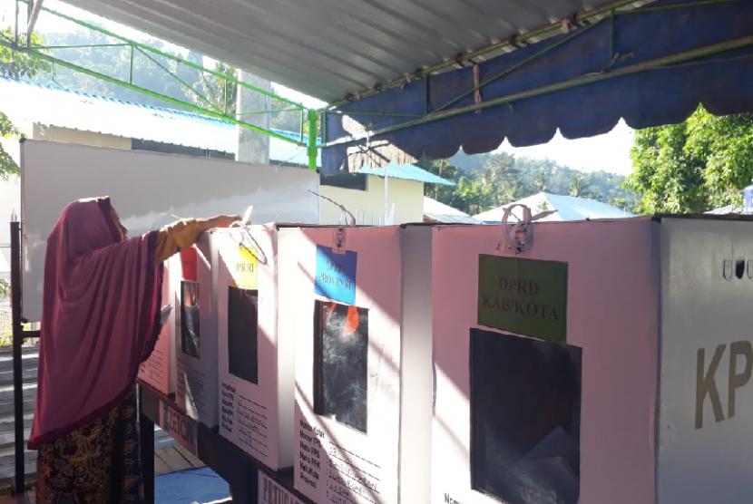 Warga terdampak gempa di Dusun Apitaik, Desa Guntur Macan, Kecamatan Gunungsari, Kabupaten Lombok Utara, NTB, melakukan pencoblosan di TPS, Rabu (17/4).