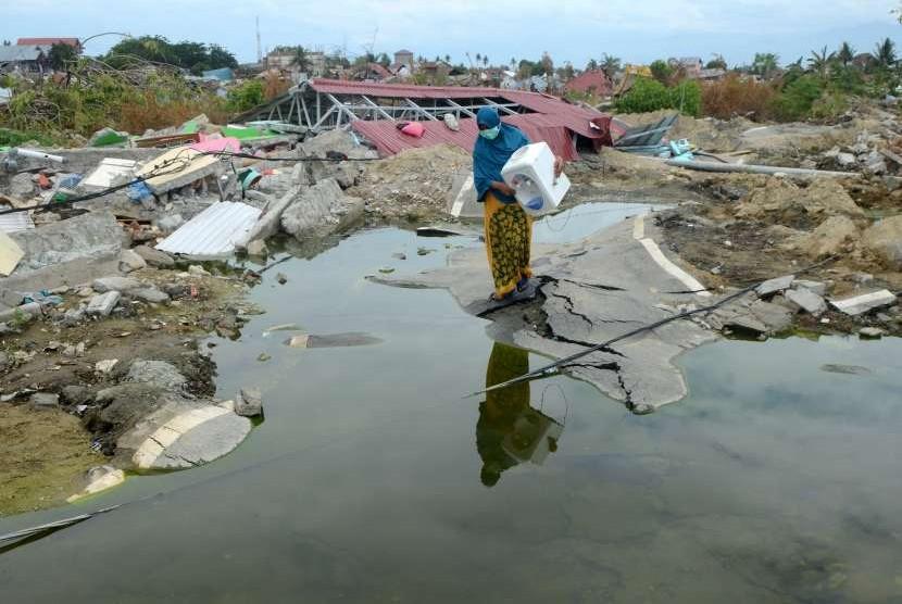 Warga terdampak gempa membawa barang layak pakai sekitaran reruntuhan rumahnya di Balarowa, Palu, Sulawesi Tengah, Kamis (11/10).