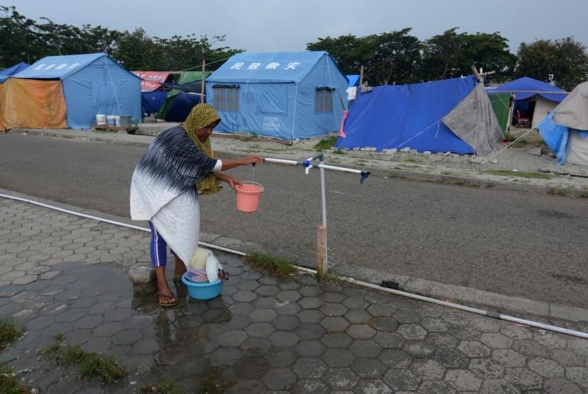 Warga terdampak gempa mencuci peralatan dapur di Kamp Pengungsian Sementara di halaman Masjid Agung Darussalam Palu, Sulawesi Tengah, Kamis (8/11/2018).