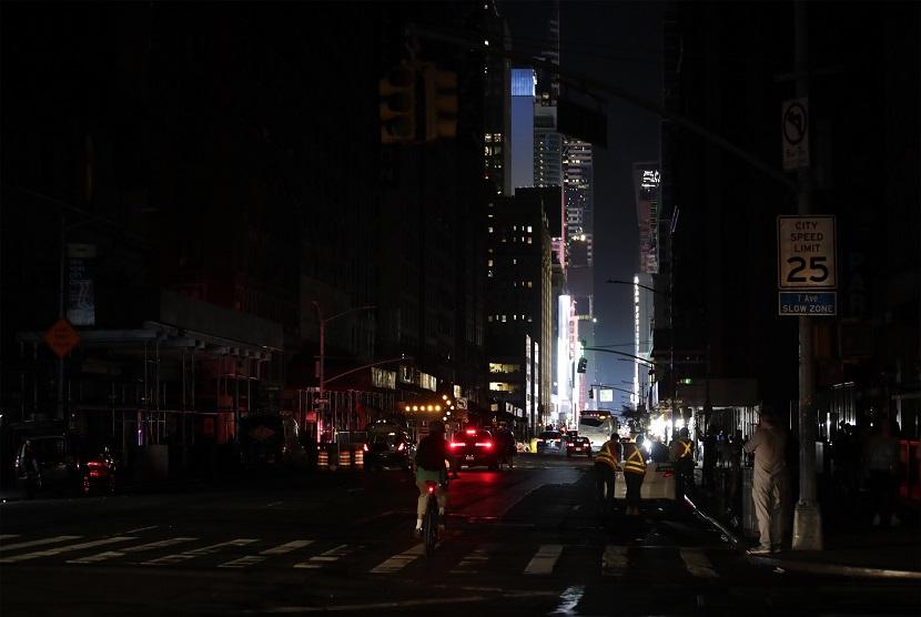 Warga terlihat berjalan kaki dan menaiki sepeda di 7th Avenue sekitar Times Square, Manhattan ketika terjadi pemadaman di New York, Amerika Serikat, Sabtu (13/1)