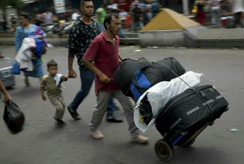 Warga Venezuela memasuki Kolombia dengan menyeberangi jembatan internasional Simon Bolivar dari San Antonio del Tachira, Venezuela, Kamis (21/2). Rakyat Venezuela mengalami kelangkaan makanan dan obat-obatan.